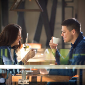 Young couple is on a romantic date in a restaurant. Two young people are drinking coffee and talking.